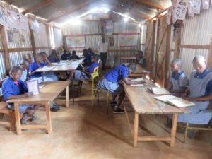 Class Five in library with teacher John Simiyu